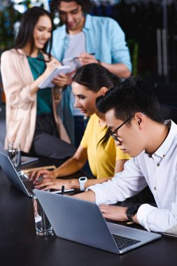 meslektaşlarının ders kitabı modern ofis yazma sırasında masada dizüstü bilgisayarlar kullanarak çok ırklı iş arkadaşları