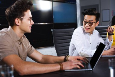 young asian businessman talking to colleague while he using laptop at modern office