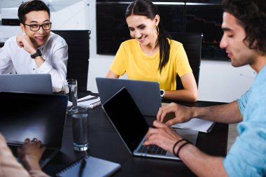 smiling multicultural group of business partner talking at table with laptops in modern office