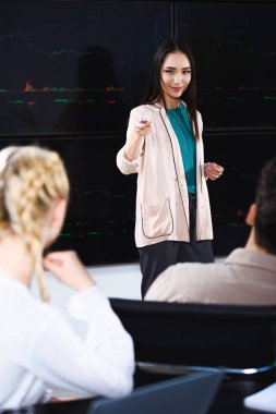 asian businesswoman showing presentation and pointing on female colleague at modern office