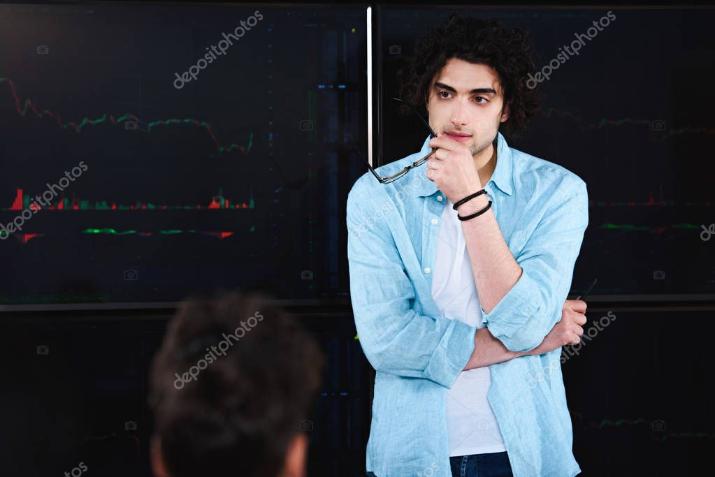 young businessman with eyeglasses in hand standing in front of board with graphics at modern office