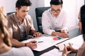 Fotografie mnohonárodnostní podnikatelé mají schůzku u stolu s grafy v moderní kanceláři