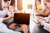 részleges kilátás nyílik üzletember gépelés-on laptop-val üres képernyő, miközben a partnerek, miután megbeszélést a modern irodai asztal