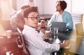 ázsiai üzletember keresi a kamera, miközben ő partnerei, miután megbeszélést, modern irodában szemüvegek