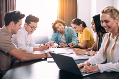 Multiethnic group of business colleagues having discussion at table with graphs in modern office stock vector