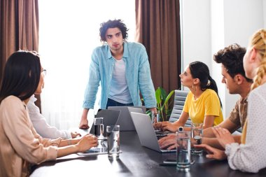 multicultural business partners having meeting at table with laptops in modern office