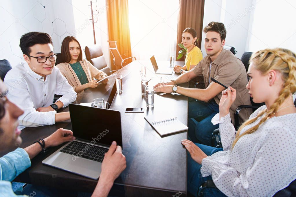 cropped image of multicultural business partners having meeting at table with laptops in modern office