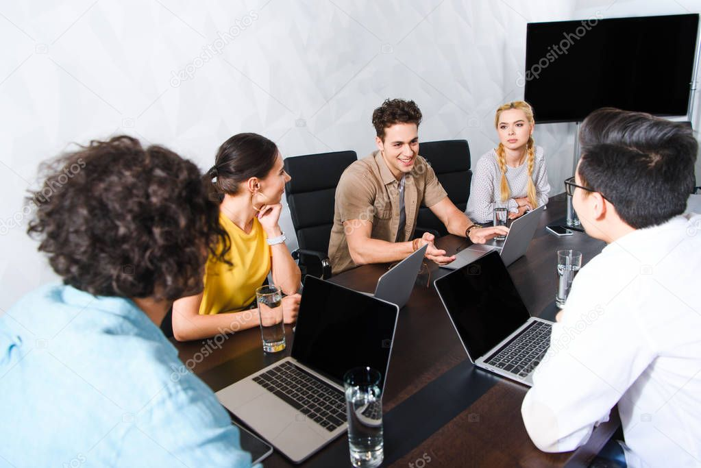 group of multicultural business people having discussion at table with laptops in modern office