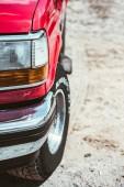 Fotografia Chiuda in su del Faro di automobile rossa sulla strada sabbiosa