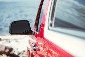 Fotografia fuoco selettivo del jeep specchio, rosso auto vicino al mare