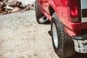 Fotografia ruote di automobile rossa sulla strada sabbiosa durante il viaggio