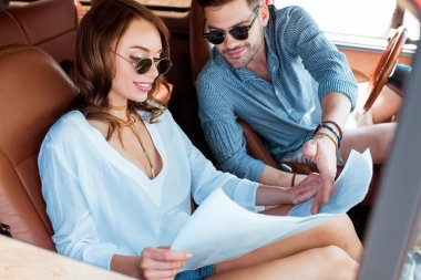 beautiful couple looking at map in car during road trip