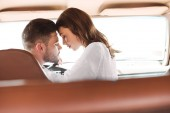 Fotografie beautiful couple with closed eyes going to kiss in car together