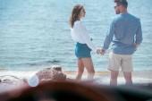 Selektivní fokus auto a mladý pár se drží ruce u moře