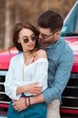 tender beautiful couple in sunglasses hugging near red car