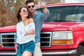 Fotografia uomo sorridente che abbraccia la sua amica e che punta da qualche parte mentre si trovava vicino jeep rossa