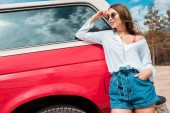 attractive girl in sunglasses posing near red car during road trip