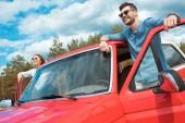Fotografia giovani coppie di viaggiatori in jeep rossa