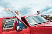 Fotografia Coppie allegre dei viaggiatori in jeep rossa