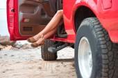 oříznutý pohled na ženské nohy v červené auto na výlet