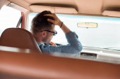 rear view of stylish man in sunglasses driving car during road trip