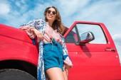 pohled zdola veselá mladá žena v sluneční brýle v červené auto
