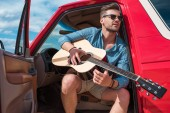 Fotografie handsome young man playing acoustic guitar in car during road trip