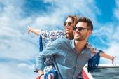 boldog ember piggybacking a mosolygós barátnője, kék ég, a háttérben