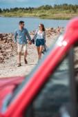 Selektivní fokus páru, drželi se za ruce a chůzi na břehu moře během výlet