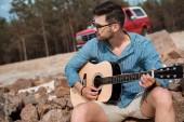Fotografia giovane uomo che gioca chitarra acustica allaperto, rosso jeep su priorità bassa