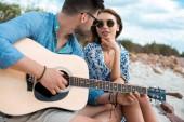 mužské kytarista hrál na akustickou kytaru a sedí s přítelkyní venku