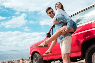 young man piggybacking his excited girlfriend near red jeep
