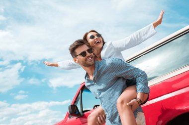 excited young couple of travelers piggybacking at car