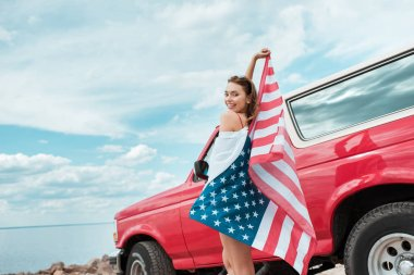 happy beautiful girl with american flag standing near red car
