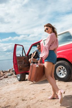 happy girl with suitcase and boyfriend with guitar near red jeep on road trip