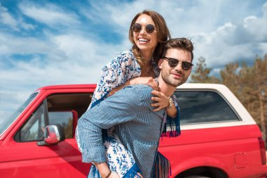young smiling couple in sunglasses piggybacking near red car