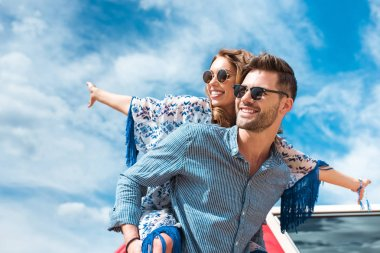 happy man piggybacking his smiling girlfriend with blue sky on background