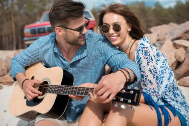 happy couple hugging while man playing acoustic guitar