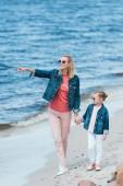 Rodina drží za ruce a chůzi na břehu moře, matka směřující někam