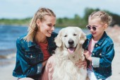 Fotografie attractive mother and smiling daughter with golden retriever dog on sea shore