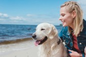 Fotografie beautiful smiling woman sitting with golden retriever dog on sea shore