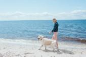 Fotografie blonde Frau zu Fuß mit golden Retriever Hund am Meer