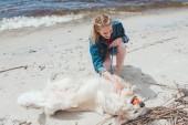 Fotografie Lächelnde Frau spielen Ball mit golden Retriever Hund am Ufer
