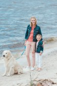schöne Familie spazieren mit Golden Retriever Hund in der Nähe des Meeres