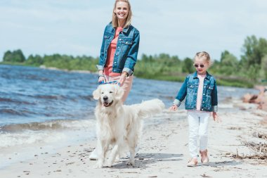 happy family walking with golden retriever dog on sea shore