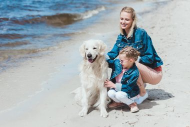 family sitting with golden retriever together on sea shore