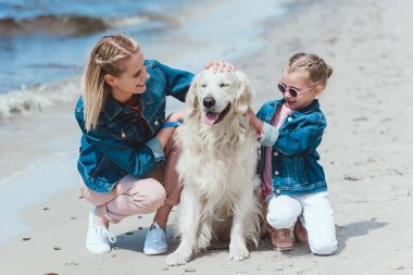 happy family sitting with golden retriever dog on sea shore