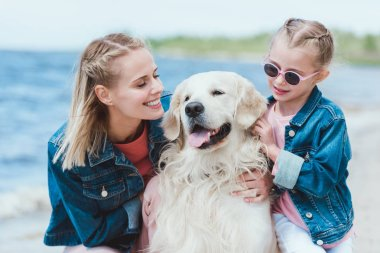 smiling mom and daughter with golden retriever dog on sea shore