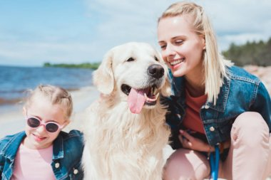 happy family sitting with golden retriever on sea shore