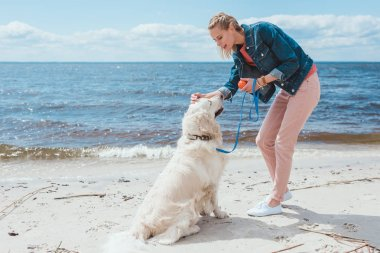 happy woman playing ball with golden retriever on sea shore